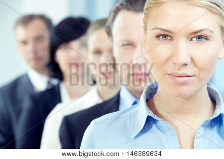 Young businesswoman looking at camera with her team on background