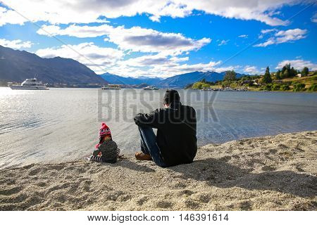 Father With Little Daughter Appreciate Lake Wanaka Landscape In New Zealand