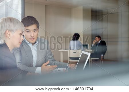 Young businessman showing his presentation on laptop to female leader