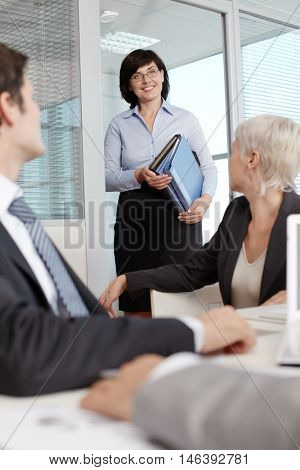 Smiling secretary carrying folders for business people