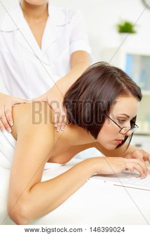 Young businesswoman working on computer and being massaged at one time