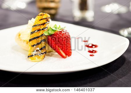 Custard cream tart dessert with fresh strawberries in a restaurant setting