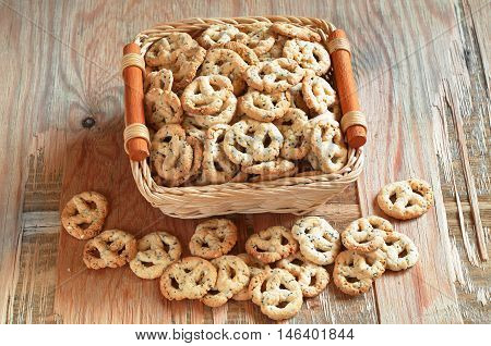 Salty pretzels with cheese and poppy in basket on old wooden table. Delicious snack for beer