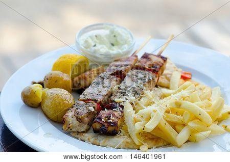 Chicken souvlaki with fried potatoes and tzatziki sauce traditional greek food on white plate