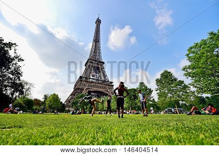 PARIS FRANCE - JUNE 8: People playing with soccer ball in Champ de Mars park near the Eiffel Tower during the UEFA 2016 European Championship on June 8 2016 in Paris.
