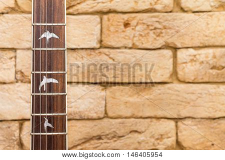 Wood guitar neck and brick on the  background