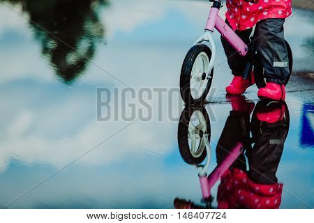 little girl riding bike in water puddle, kids seasonal activities