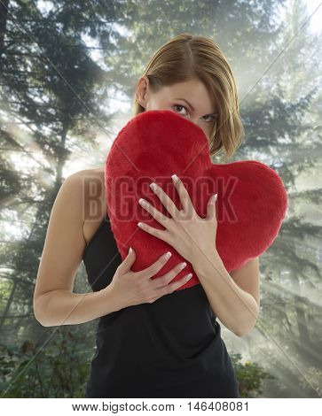 Young beautiful woman hiding behind a red heart shaped pillow with sunbeams through a green forrest in the backgorund