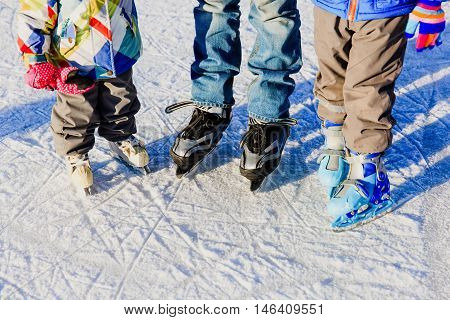 father with two kids skating in winter snow, family winter sport