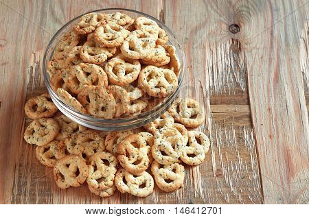 Salty pretzels with cheese and seed in glass bowl on old wooden table. Tasty snack for beer