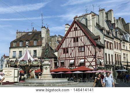 Famous Fountain, Characteristic Houses And Colorful Carousel In Dijon, Burgundy, France. Place Franc