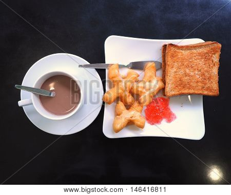 Breakfast with hot cocoa; deep-fried dough stick or Patongko with Sweetened condensed milk and toast with strawberry jam