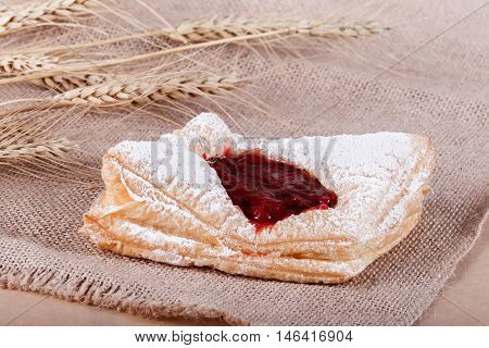 Fresh Puff Pastry With Powdered Sugar With Jam On Rustic Background With Spikelets