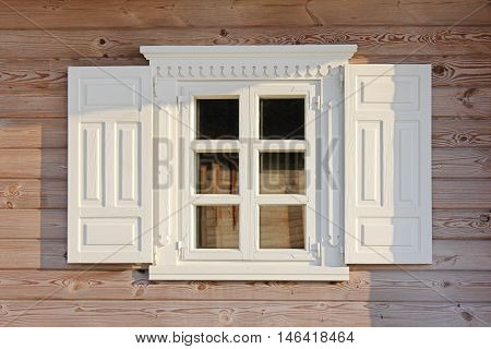 Wooden window with beautiful white shutters under olden. Wall of the rural house.
