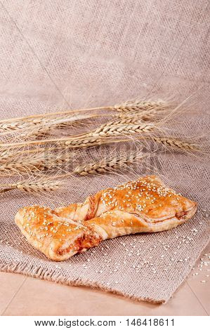 Delicious Puff Pastry With Cheese Filling And Sesame Seeds On Rustic Background With Spikelets