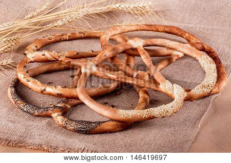 Fresh Pretzels With Poppy Seeds, Cinnamon, Sunflower Seeds And Sesame Seeds On Rustic Background Wit