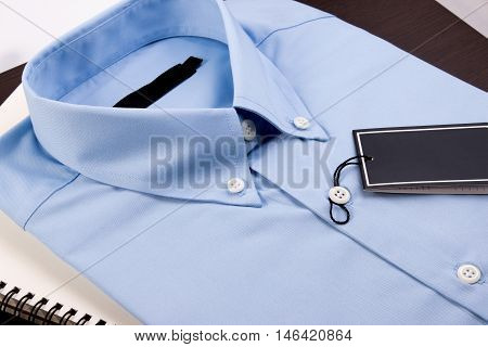 Blue Shirt And Notebook On Wooden Background. Blue Shirt With Black Blank Price Tag On Wooden Table.