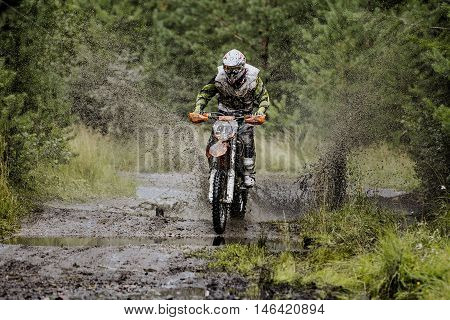 extreme racer on a motorcycle rides puddle water splashes and dirt. competitions on Enduro in woods