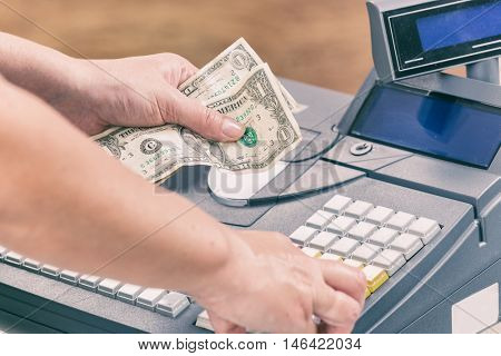 Cashier holdnig banknotes and using cash register at shop