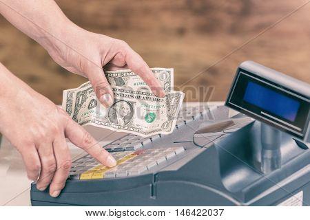 Cashier holdnig banknotes and using cash register at shop