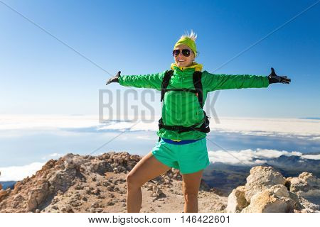 Woman successful hiking climbing in mountains motivation and inspiration landscape on island and ocean. Female hiker with arms up outstretched on mountain top looking at beautiful view on Teide in Tenerfie Spain.