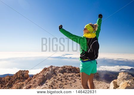 Successful hiking climbing woman with backpack on Teide mountain top Tenerife. Looking at inspirational landscape view. Hiker arms outstretched. Fitness and sports motivation Canary Islands.