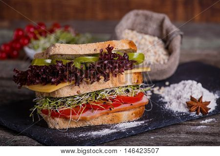 Sandwich With Cereals Bread With Lettuce, Slices Of Fresh Tomatoes And Sweet Pepper, Ham, Prosciutto