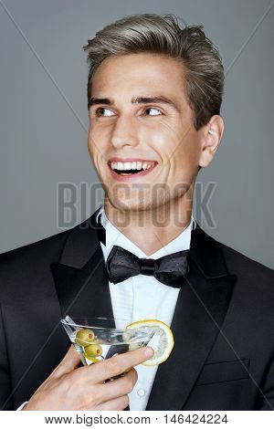 Laughing imposing man with glass of martini looking away. Photo of Stylish man in elegant black suit. High life