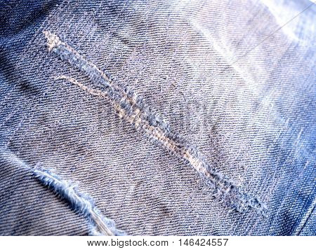 Denim jeans texture or denim jeans background with old torn. Old grunge vintage denim jeans. Stitched texture denim jeans background of fashion jeans design. Dark edged.