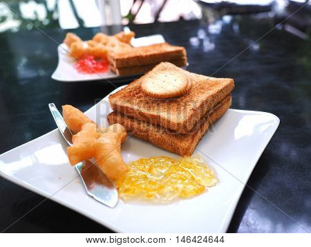 Breakfast with deep-fried dough stick or Patongko with Sweetened condensed milk and toast with marmalade and strawberry jam