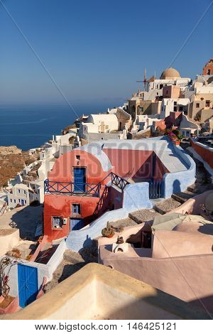 Oia Santorini with sea and caldera on background. Vertical shot