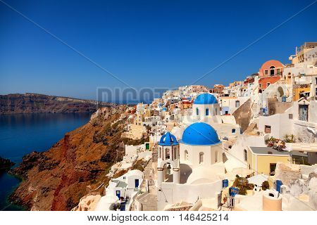 Landscape of Oia town in Santorini Greece with blue dome churches on foreground. Vertical shot