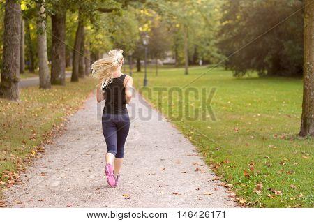 Fit Active Young Woman Jogging Through A Park