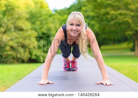 Fit Young Blond Woman Doing Exercises In A Park