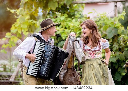 Couple in traditional bavarian clothes standing by an old wooden horse in green garden, man playing accordion. Oktoberfest.