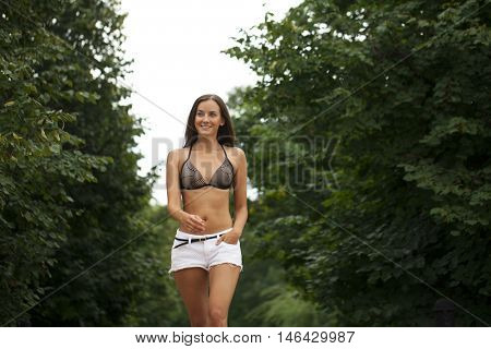 Closeup portrait of young brunette woman in white short, summer park outdoors
