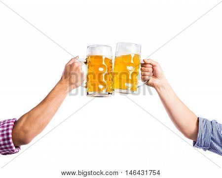 Hands of two unrecognizable men clinking with beer mugs. Oktoberfest. Studio shot on white background, isolated.