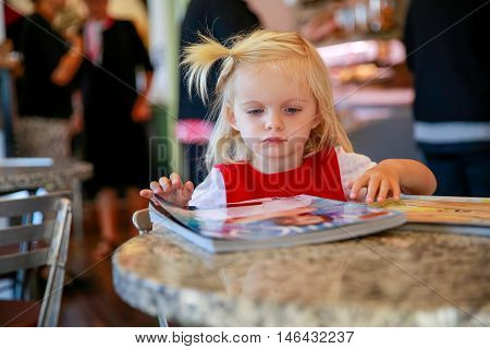 Sweet Little Blond Girl Looks Magazine In A Cafe