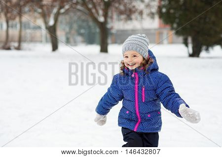 Cute little girl in blue jacket and knitted hat playing outside in winter nature, running around