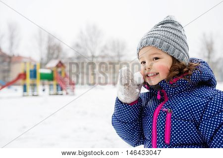 Cute little girl in blue jacket and knitted hat playing outside in winter nature