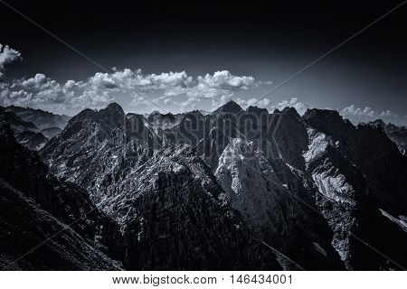 View on summit peaks from dark contrasty view on the Alps in Allgau Germany, Europe