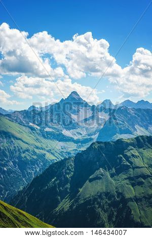 Deep valley with green foothills and mountains of the Alps under white scattered clouds in Germany