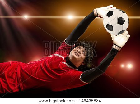 Portrait of goalkeeper in jump catching ball