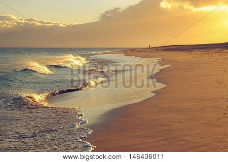 View of the beach in Morro Jable Fuerteventura with golden sand a figure of a walking person far away and strong vawes in the Atlantic ocean and on the sunset.