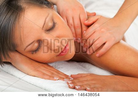 Young woman having a classical massage lying on white bed. Detail on face
