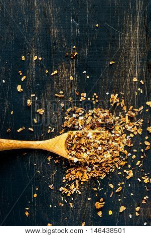 Seasoning. A mixture of salt and spices for cooking, with a wooden spoon for spices on a black wooden table. top view