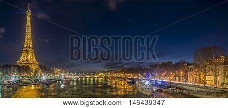 Paris France - February 14 2016: Night cityscape with the Seine River and Eiffel Tower in Paris France on February 14 2016.