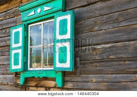 Brightly painted window in the village house stands out against the old wooden walls.