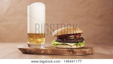 homemade burger with marble beef, sweet onion, cheese and vegetables served with lager beer, wood table