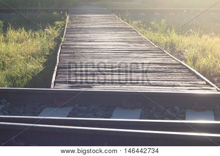 The wooden bridge over the railway with the evening sun